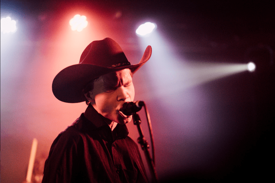 Geordie Greep, member of the rock band Black Midi, wears a cowboy hat and sings into a microphone with his eyes closed