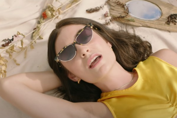 New Zealand Singer Lorde lying back wearing sunglasses and a yellow dress