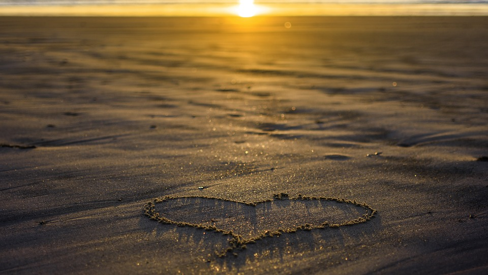 heart in sand, low sun in the background