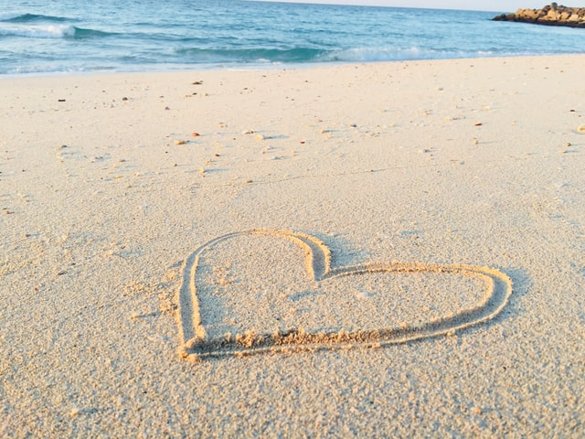 heart shape in the sand with the sea in front