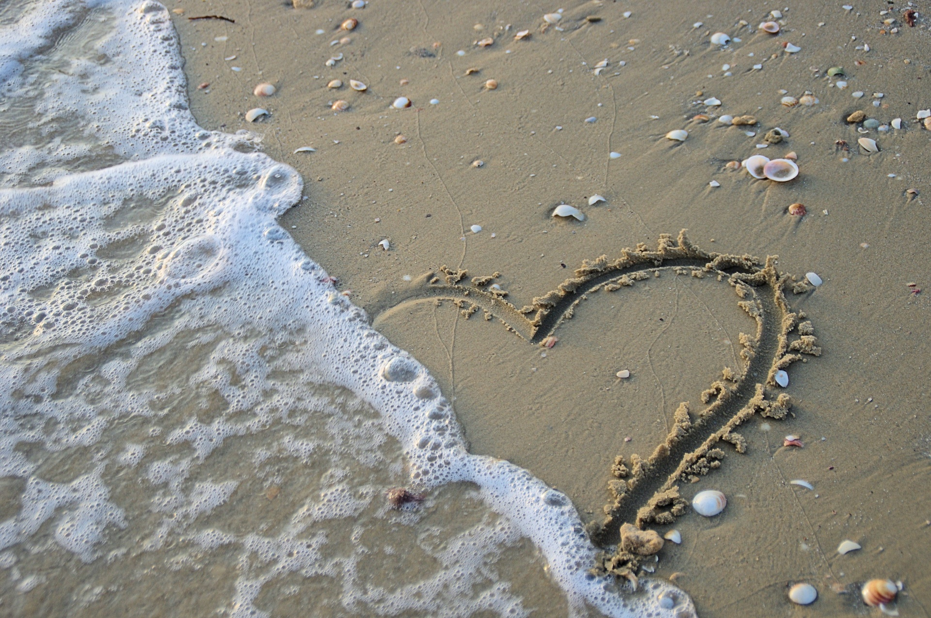 Wave washing out a heart drawn in the sand