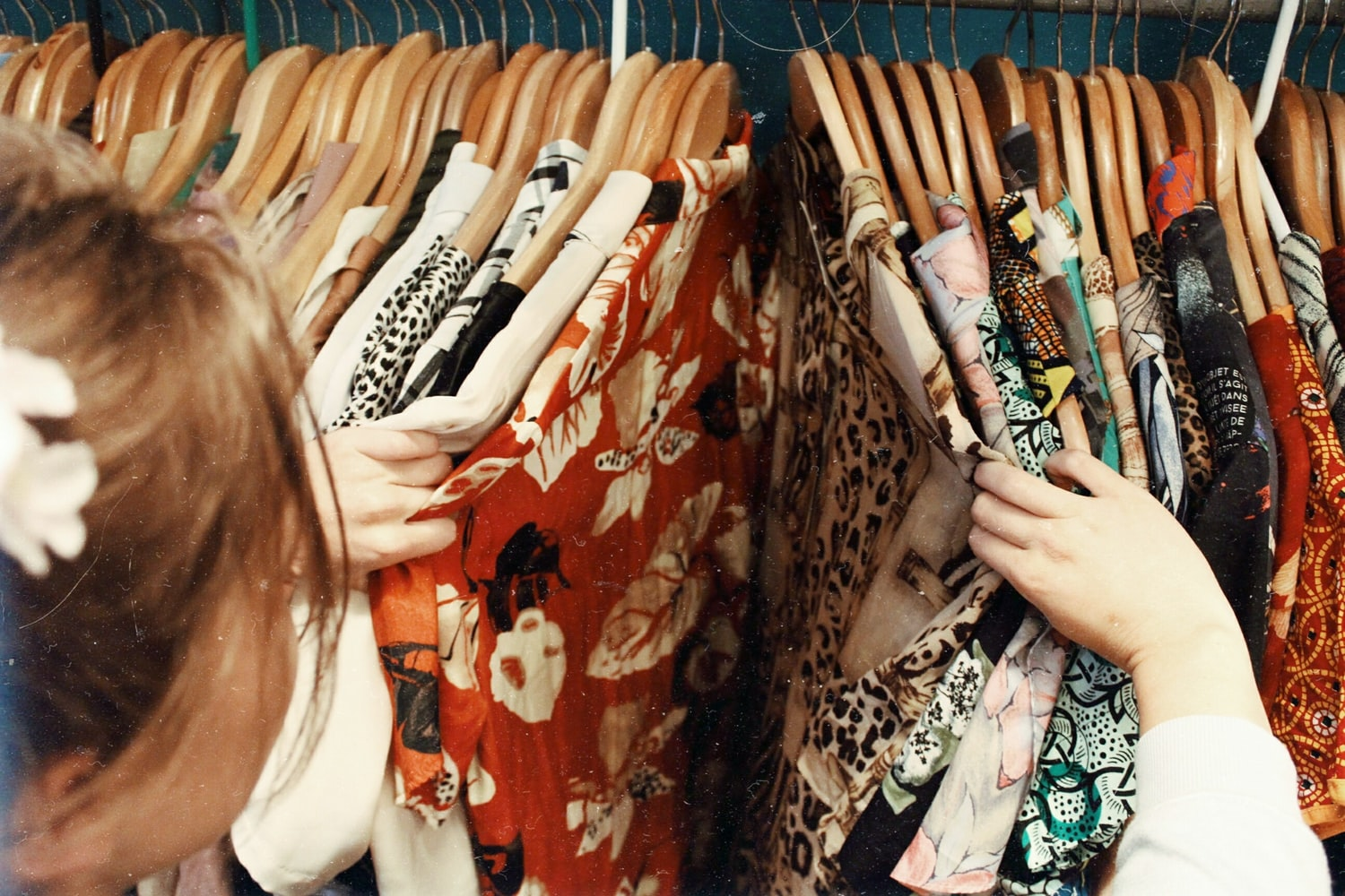 Person looking at clothes hung on a rack