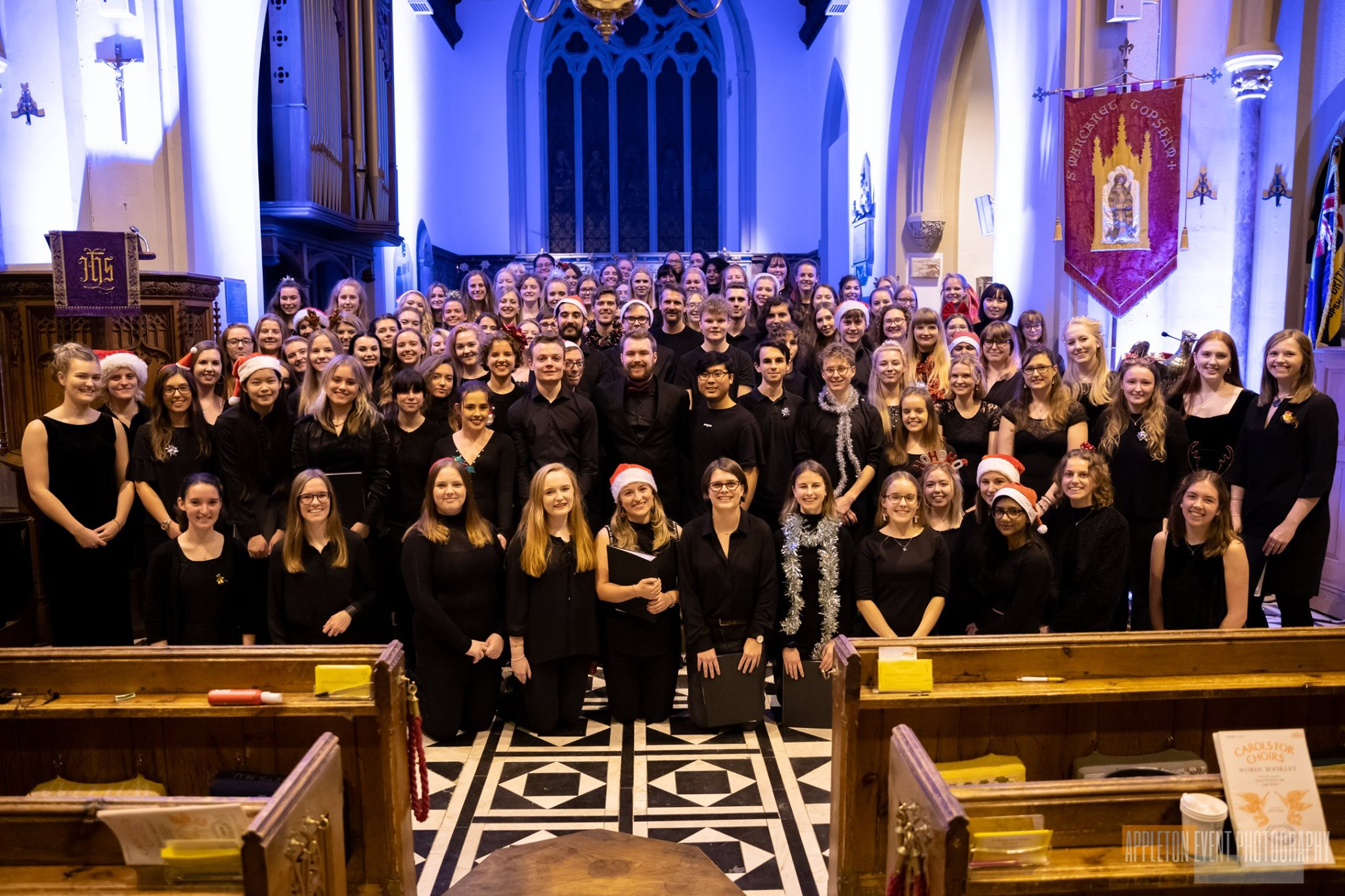 A large choir smiling at the camera and assembled in a church for a Christmas concert
