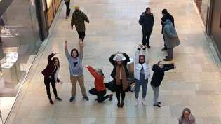 A group of people standing up and forming the word choir with their bodies