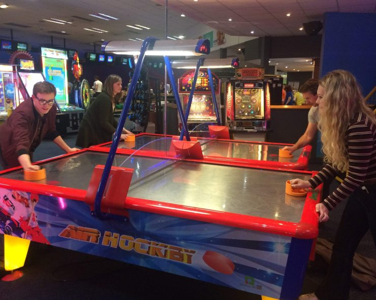 Four people playing air hockey indoors