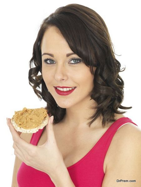 Young Woman Eating Peanut Butter on a Cracker