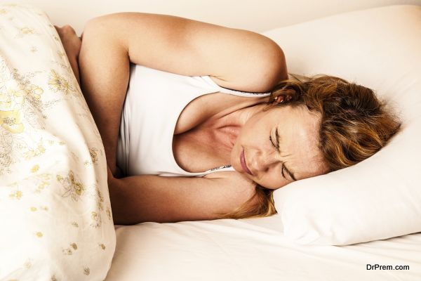 Woman feeling sick with stomachache in bed - Pain in stomach