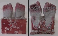clay feet in red box with ice cubes and debris, feet are red and grazed