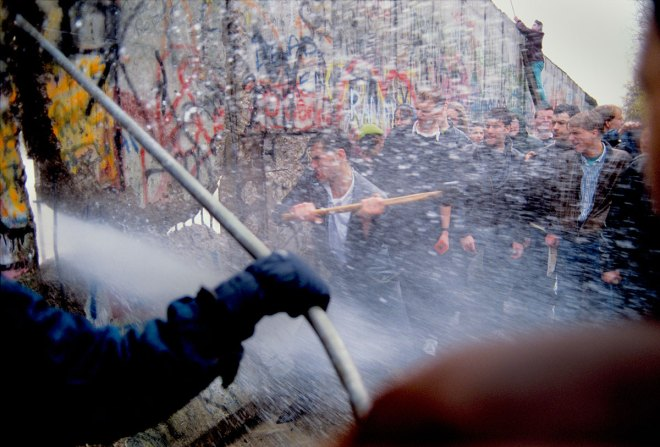 Alexandra Avakian Young West German Men Attack the Berlin Wall while East German Guards Shoot Water Cannon through the Cracks, 1989 Collection of the Artist