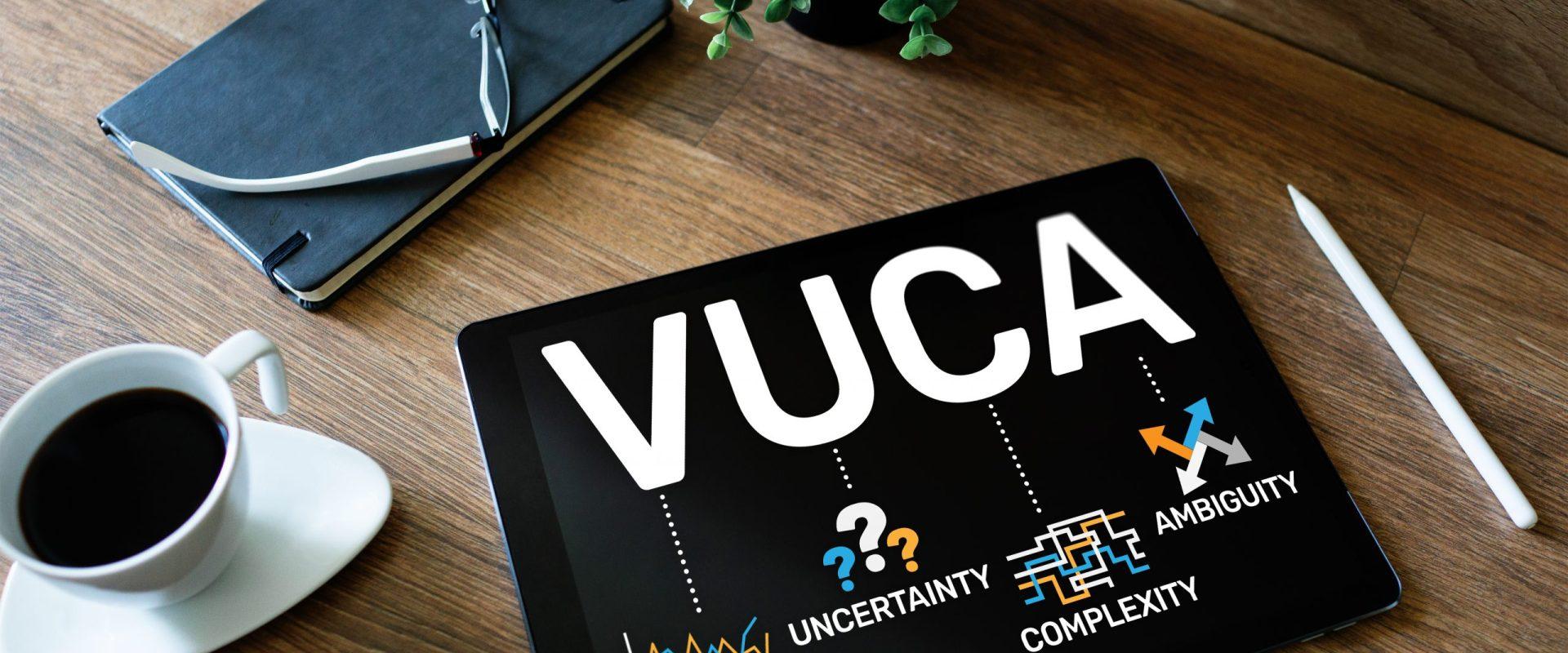 Auf einem iPad stehen die Buchstaben V U C A. Die Abkürzung steht für volatility, uncertainty, complexity und ambigouity. Daneben steht eine Tasse Kaffee. Darüber liegt ein Notizbuch, auf dem eine Brille liegt.