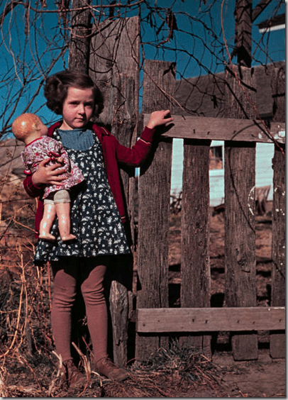Girl with doll standing by fence