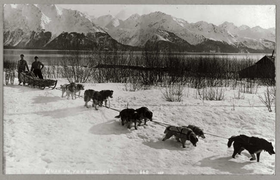 Dog team pulling a sled through a snow-covered field, with two men with snow shoes posed behind; snow-covered mountains and placid lake in background. Frank and Frances Carpenter Collection — Lib. of Congress Prints and Photographs Division