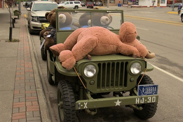 Four big teddy bears in a real jeep with a stuffed moose on the hood, West Yellowstone, Montana, August 20, 2014