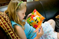child reading dressing up box book