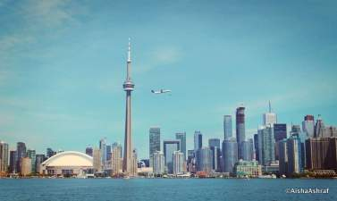 A plane flies over the harbour as it leaves Billy Bishop airport