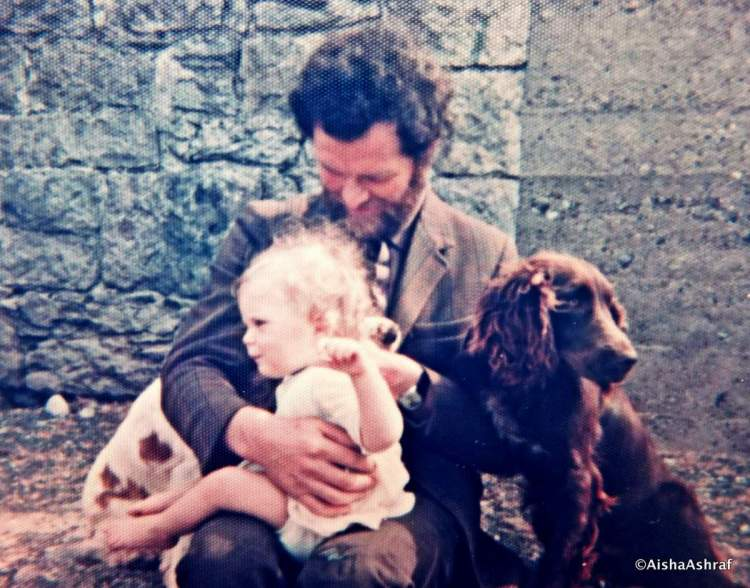 Man holding young child, with dogs