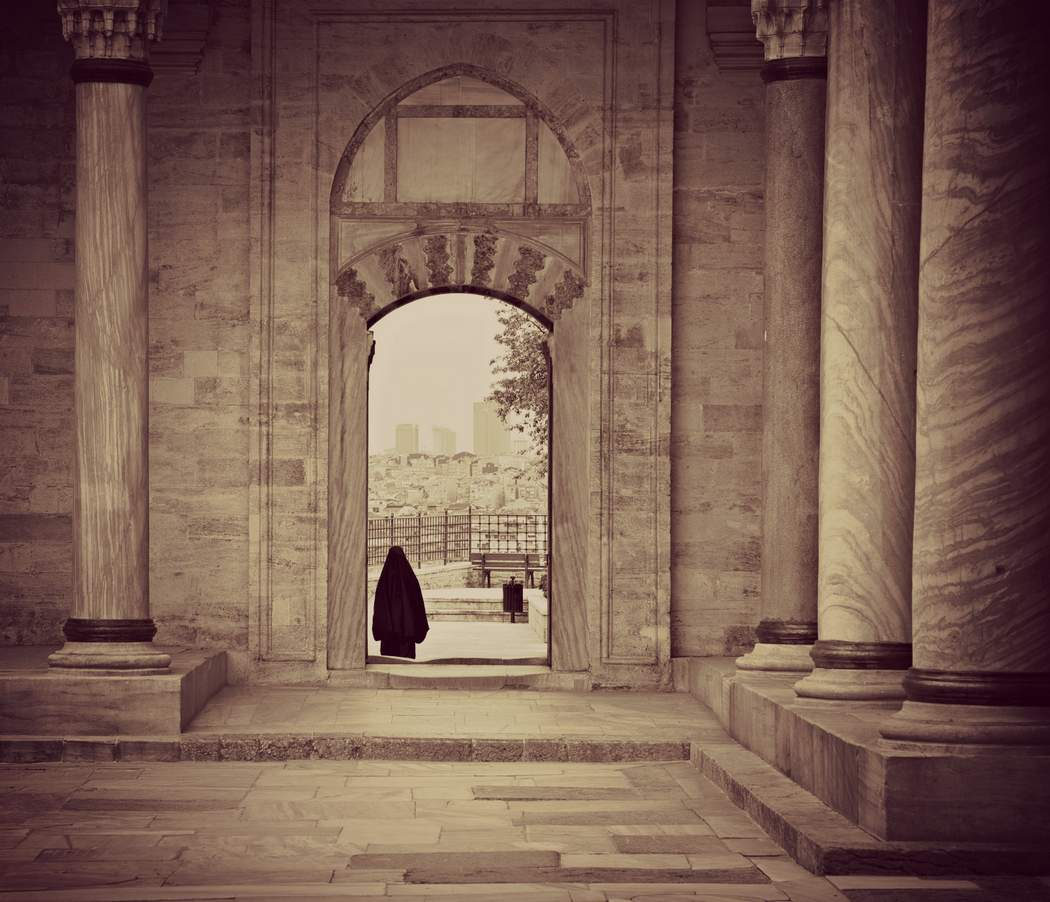Silhouette of a shrouded women through the doorway of a Turkish mosque
