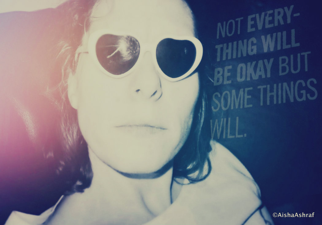 Woman in novelty sunglasses stares into the camera
