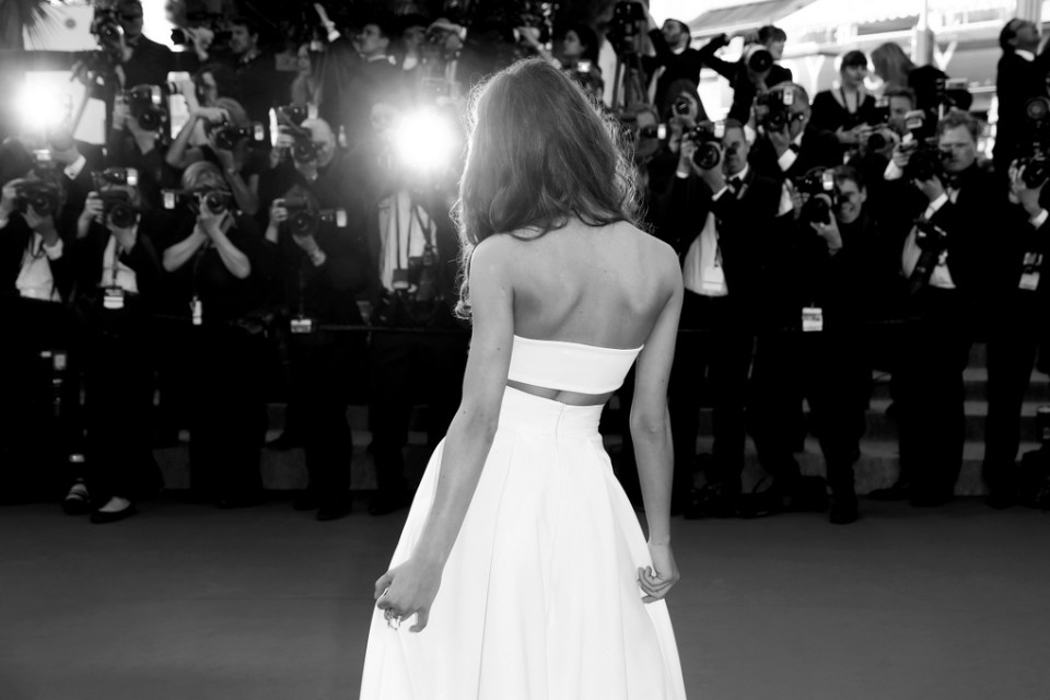 A woman in a white dress with her back to the camera facies a wall of photographers