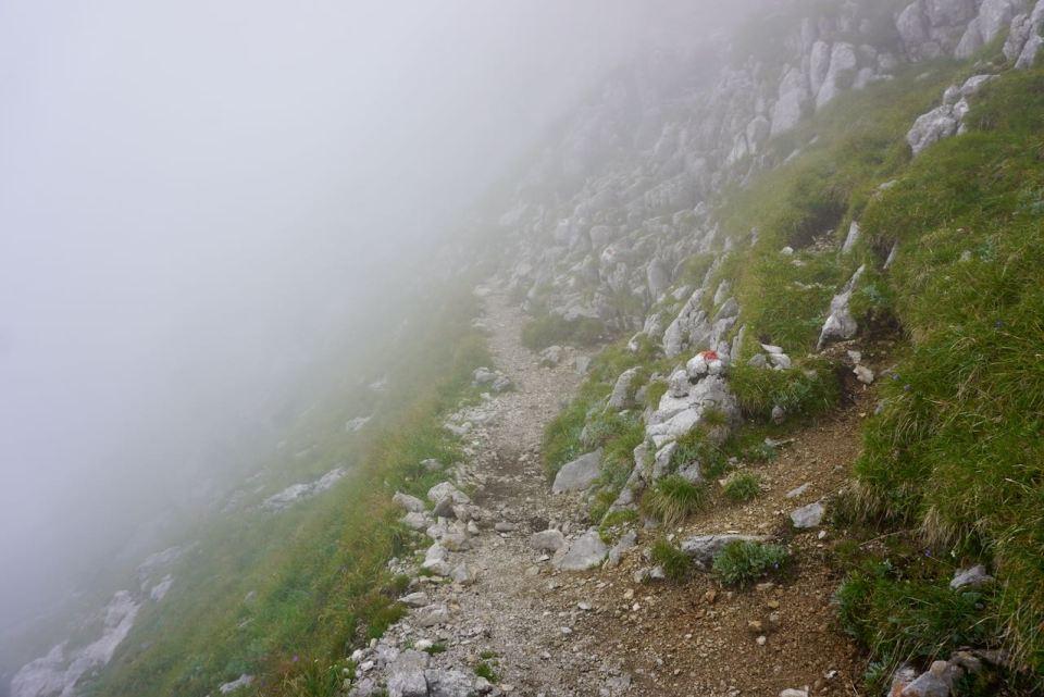 Dicht am Abhang führt der Weg durch tiefhängende Wolken