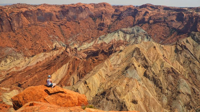 A GIRL SITTING ON THE EDGE OF A CLIFF AT UPHEAVAL DOME, CANYONLANDS NATIONAL PARK