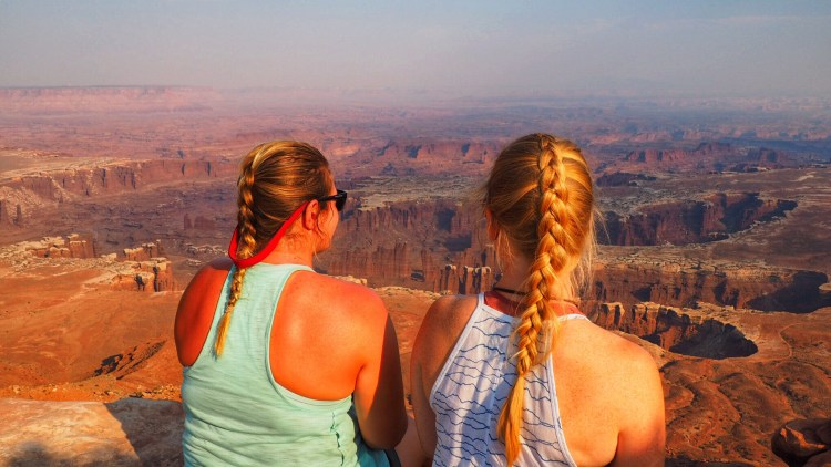 TWO GIRLS WITH BRAIDS ENJOY WHITE RIM OVERLOOK IN CANYONLANDS NATIONAL PARK