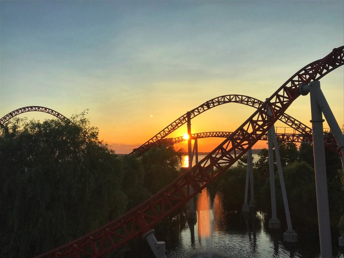sunset behind a roller coaster track