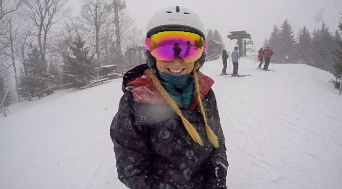 girl smiling at top of ski lift