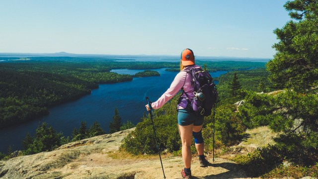Girl with trekking poles on mountain overlook salt water lake