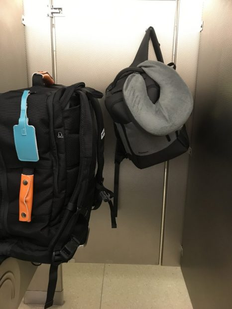 Standard Luggage travel bags hanging perfectly in an airport bathroom stall.