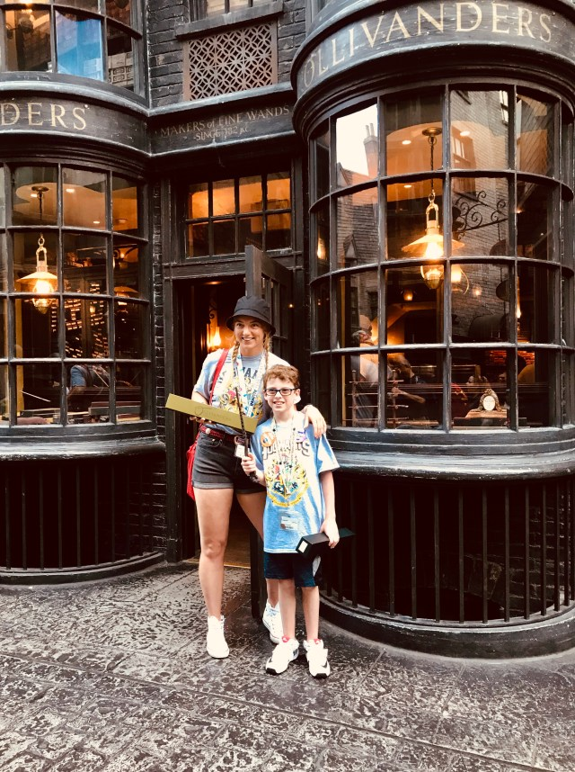 A brother and sister holding their brand new interactive wands outside of ollivanders.