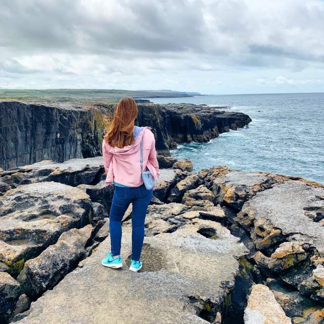 Woman standing on edge of cliffs at the Cliffs of Maher in Ireland