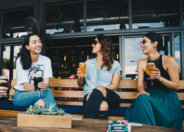 Three women introverts having a drink together and laughing