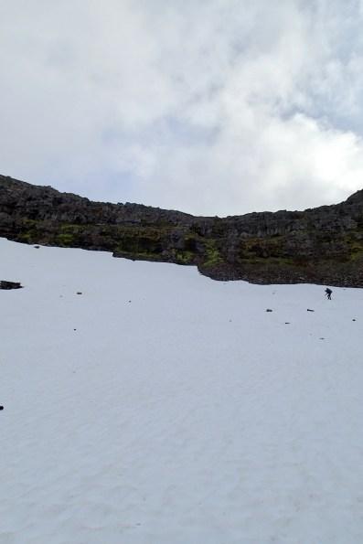 Połać śniegu pod barierą skalną.