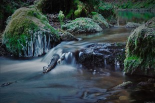 Long exposure of a small cascade in the Jura mountains on a cold day in winter - exploring the headwaters