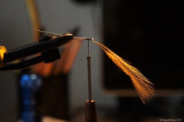 Attaching feathers with thread to the headpins in the vice