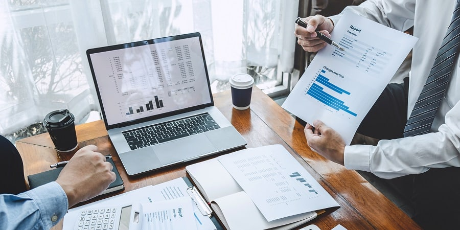 Pictured: two business professionals are at a desk conducting a spend analysis, examining what they are spending by category.