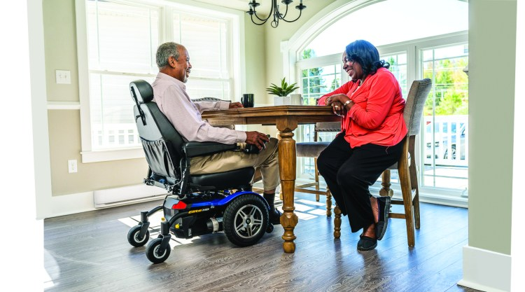 Man in a power chair speaking to woman at dining room table.