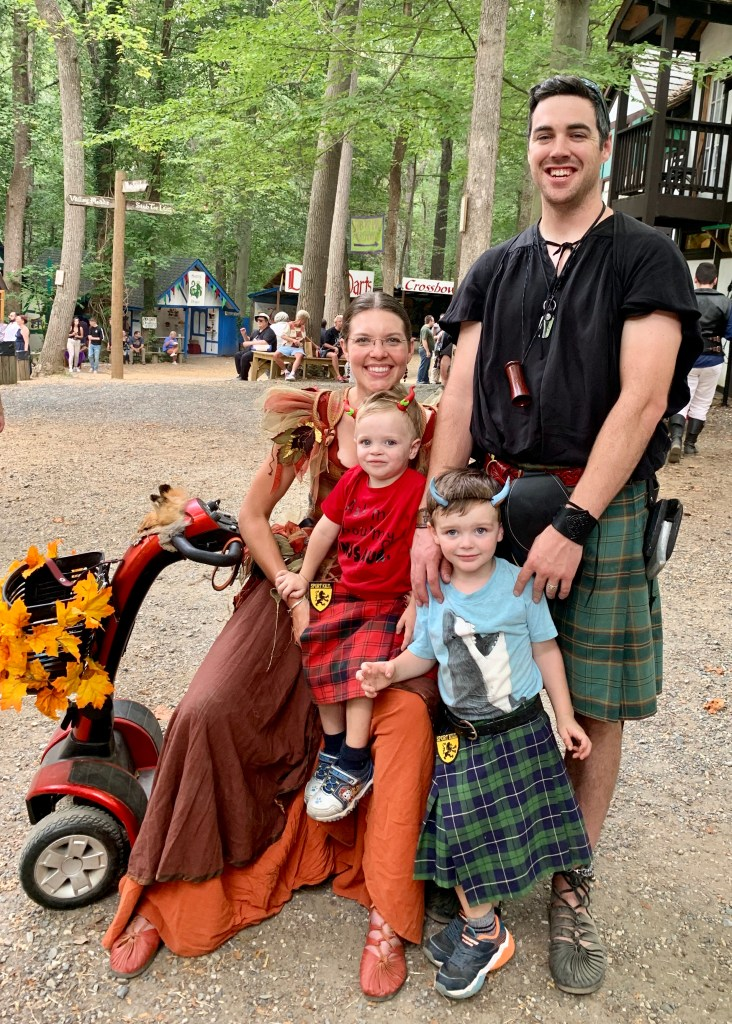 Veronica Gogan and her family posing in kilts while she is on her mobility scooter.