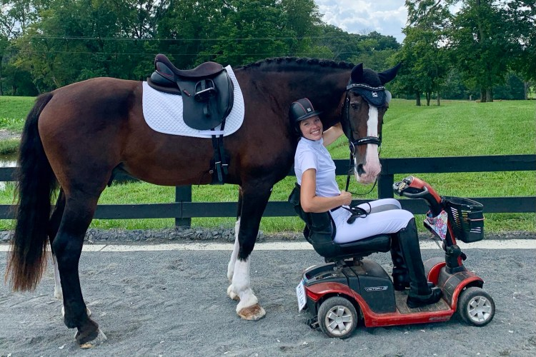 Veronica Gogan on a mobility scooter with her horse being lead beside her.