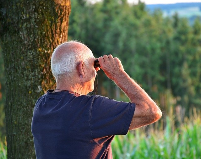 Senior man looking through binoculars on a hike