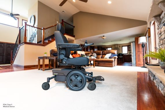 Jazzy EVO power wheelchair in black in living room on a white carpet