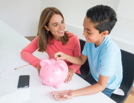 Woman teaching his boy to save money
