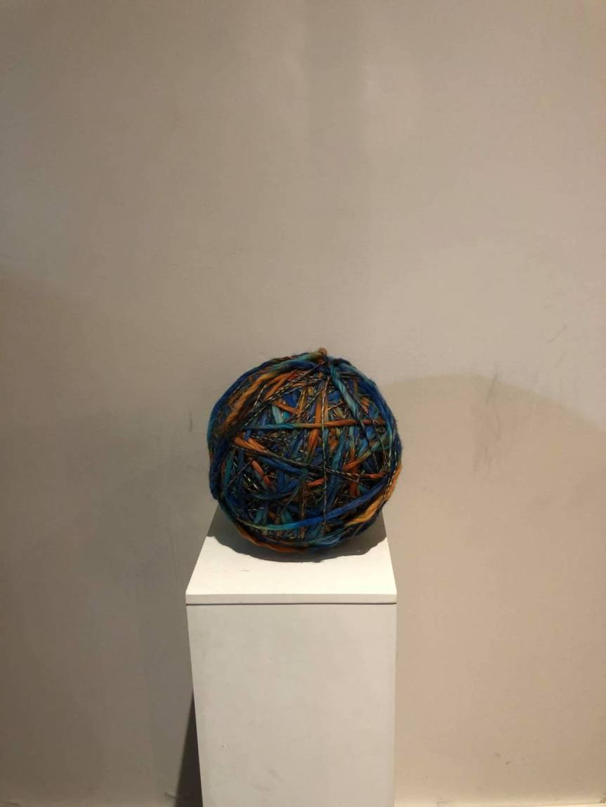 One Kilometer's worth of yarn wound into a ball, presented on a pedestal in my basement.