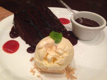 Devil's cake - Bolo de chocolate belga meio amargo. Servido com sorvete de creme e ganache de chocolate. Foto: ExperiMenteSP
