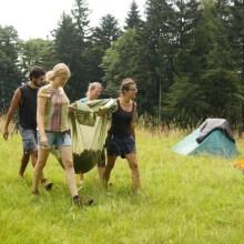 Menschen tragen Laub auf einer Plastikplane für die Wildnis-Matratze.