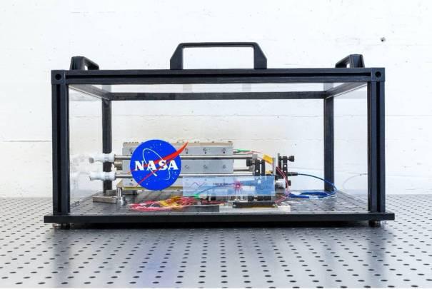 Прототип лазера находится в стеклянном ящике на перфорированном металлическом столе.