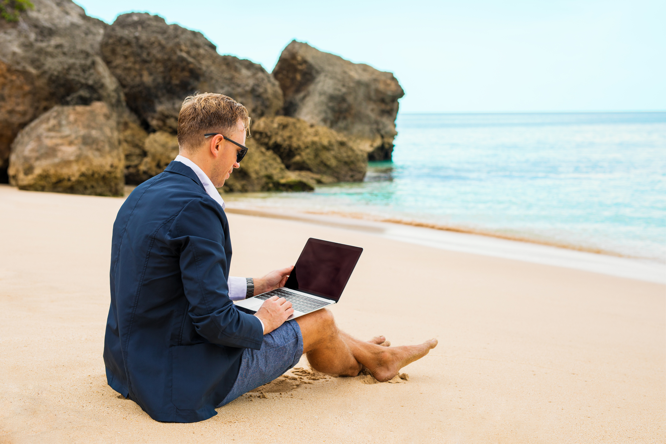 Businessman working with laptop on the beach