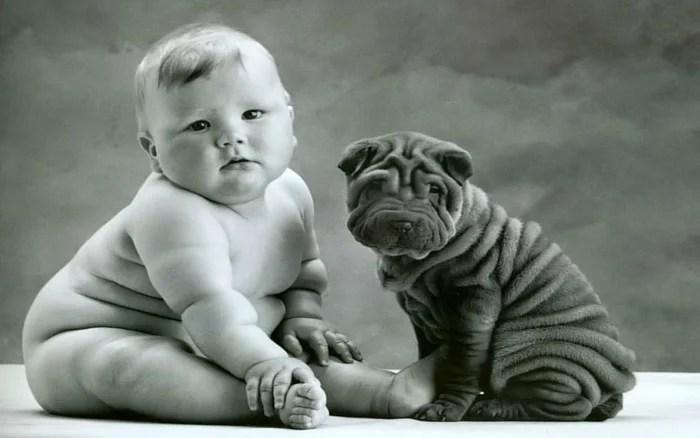 Anne Geddes portrait en noir et blanc d'un bébé potelé posé à côté d'un chiot