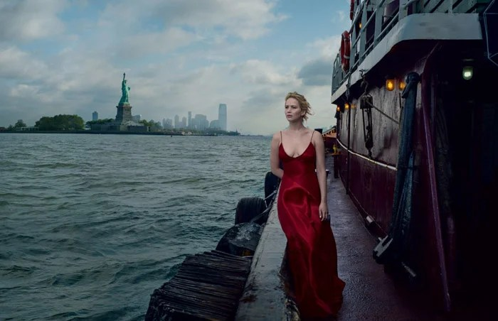 Annie Leibovitz portrait d'une fille en robe de soirée rouge debout sur un quai avec la mer et l'Empire State Building derrière elle